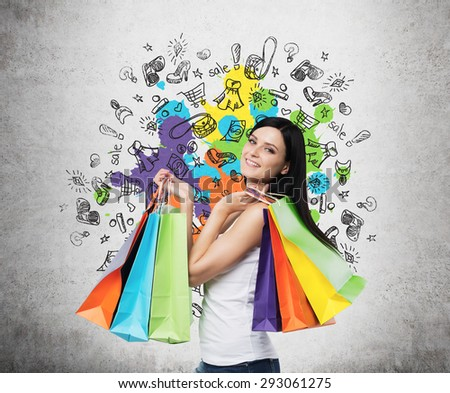 Beautiful smiling young woman with the colourful shopping bags from the fancy shops. Concrete background with drawn shopping icons. - stock photo