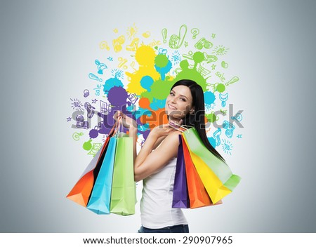 Beautiful smiling young woman with the colourful shopping bags from the fancy shops. Studio background with drawn shopping colorful spots. - stock photo