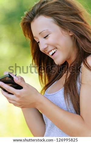 Beautiful smiling young woman writing with stylus on device, against background of summer green park. - stock photo