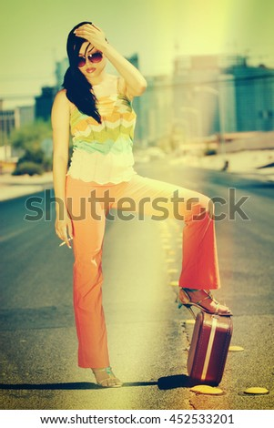 Beautiful smoking hitchhiking woman with suitcase - stock photo