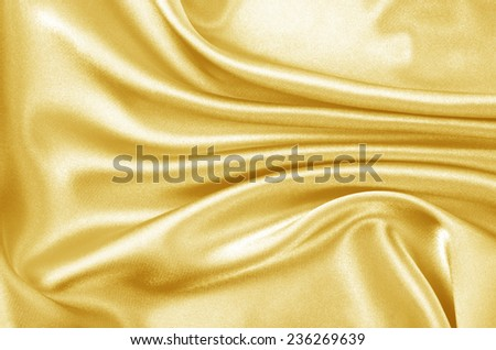 Beautiful smooth golden silk, drapery textile background - stock photo