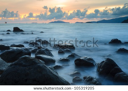 Beautiful smooth wave with black stone foreground at tropical island, Koh Lipe, Andaman sea, Thailand