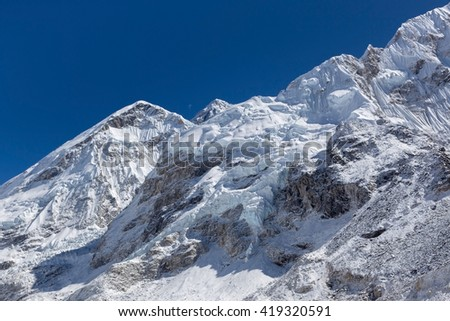 Beautiful snow and ice covered mountains view up to the peaks and blue sky from Everest Base Camp, Himalayas, Nepal. - stock photo