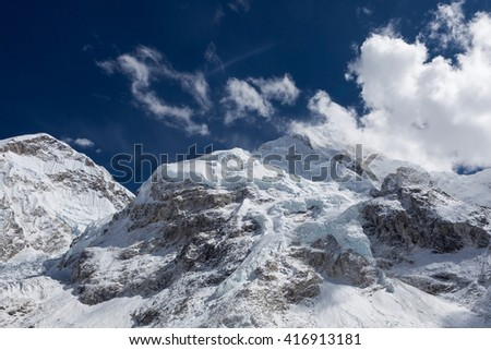 Beautiful snow and ice covered mountains view up to the peaks and blue sky with white clouds from Everest Base Camp, Himalayas, Nepal. - stock photo