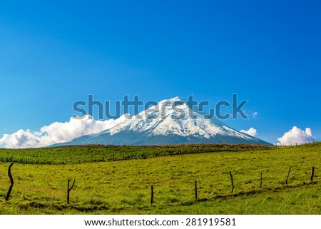 Beautiful snow capped Cotopaxi Volcano with fields in the foreground in Ecuador - stock photo