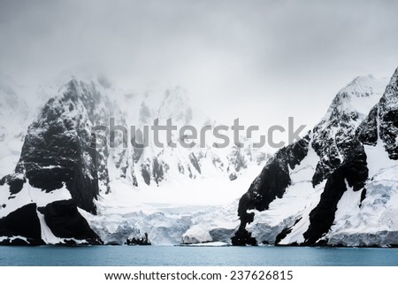 Beautiful snow-capped mountains against the white fog in Antarctica - stock photo