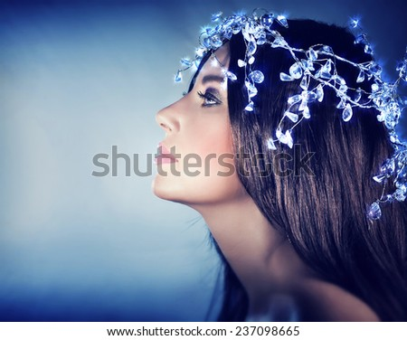 Beautiful snow queen portrait, profile of a gorgeous female wearing stylish shiny head accessories over blue background, fashion for Christmas holidays - stock photo