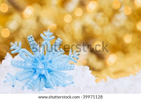 Beautiful snowflake ornament in snow with bright Christmas lights bokeh in the background. Room for text. - stock photo