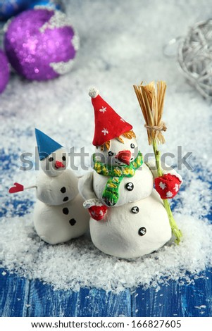 Beautiful snowmen and Christmas decor, on bright background - stock photo