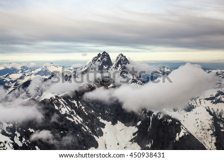 Beautiful snowy mountains of British Columbia, Canada, covered in clouds. Taken near Vancouver, during a cloudy evening before sunset. - stock photo