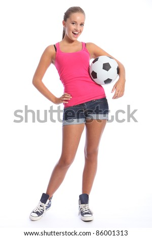 Beautiful soccer player teenage girl with happy smile wearing pink vest and denim shorts, standing with sports ball. Full length shot against white background. - stock photo