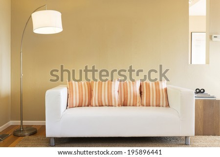 Beautiful sofa in white, with orange pillows framed by modern light, wooden stand, binoculars, books in sumptuous style home. - stock photo