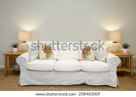 Beautiful sofa in white, with ornamented pillows framed by modern light, wooden stand, in sumptuous style home. - stock photo