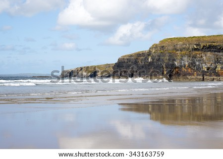 beautiful soft waves break on the beach cliffs at ballybunion - stock photo