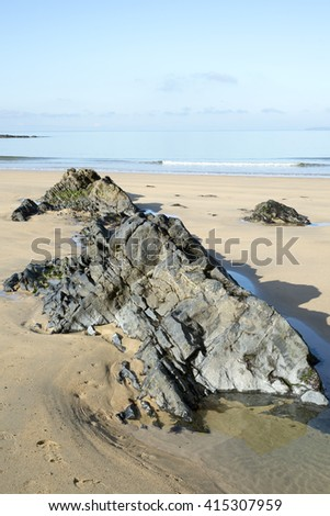 beautiful soft waves break on the black rocks at ballybunion beach in ireland - stock photo