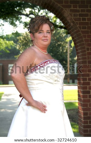 Beautiful 30 something bride in her wedding dress outside on a summer day.  Used a selective focus and a shallow depth of field. - stock photo