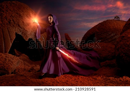 Beautiful sorceress with magical sword in chocolate mountains - stock photo