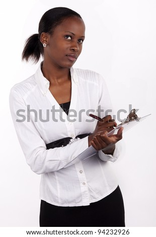 Beautiful South African woman making notes on her notepad, with a thoughtful expression. - stock photo