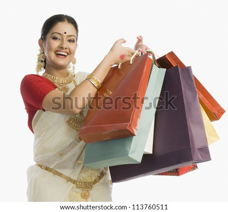 Beautiful South Indian woman holding shopping bags and smiling - stock photo