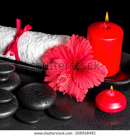beautiful spa background of hibiscus flower with dew, red candles and white rolled towel tied with ribbon on zen stones, closeup - stock photo