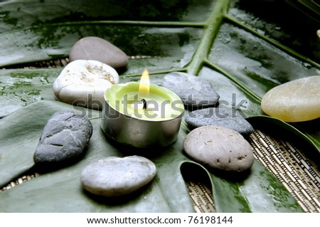 beautiful spa background- zen stones and candle with green leaf on mat - stock photo