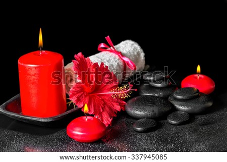 beautiful spa composition  of hibiscus flower with dew, red candles and white rolled towel tied with ribbon on zen stones - stock photo