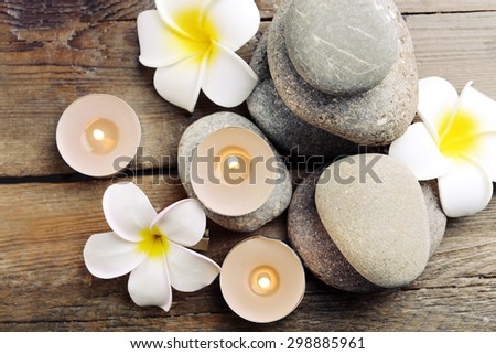 Beautiful spa composition with candles and flowers on wooden table close up - stock photo
