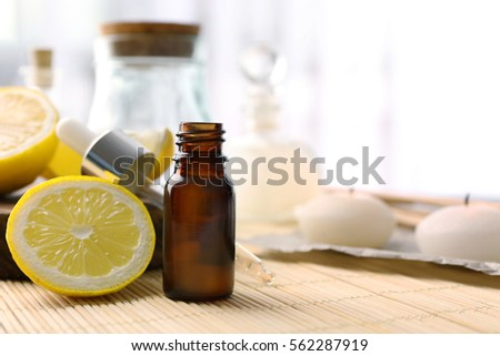 Beautiful spa composition with lemon essential oil on straw mat, closeup