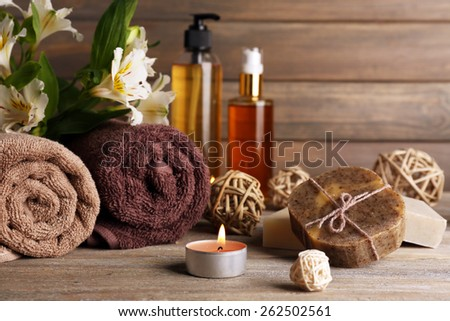 Beautiful spa composition with soap and candle on wooden background - stock photo