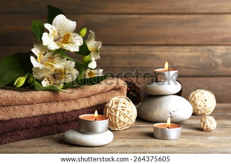 Beautiful spa composition with stones and flowers on wooden background - stock photo