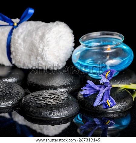 beautiful spa concept of blooming iris flower, candle, white towel and black zen stones on ripple reflection water, closeup  - stock photo