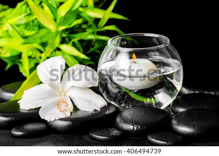 beautiful spa concept of dew white hibiscus flower, bamboo and candles in vase with water on zen stones - stock photo