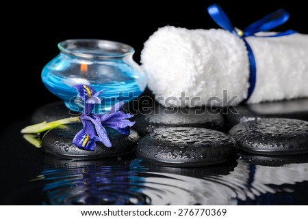 beautiful spa concept of iris flower, blue candle, white towel and black zen stones on ripple reflection water, closeup - stock photo