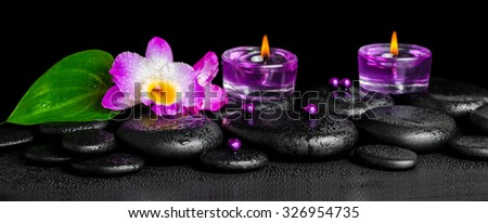 beautiful spa concept of purple orchid dendrobium with dew on black zen stone, green leaf, beads and lilac candles, panorama  - stock photo