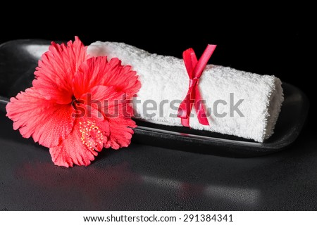 beautiful spa concept of red hibiscus flower with dew and white rolled towel tied with a ribbon - stock photo
