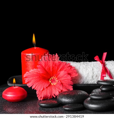 beautiful spa concept of red hibiscus flower with dew, candles and white rolled towel tied with a ribbon on zen stones, closeup - stock photo