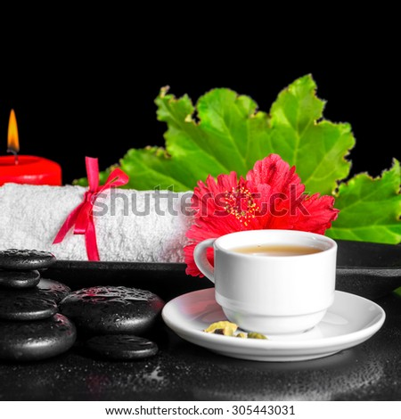 beautiful spa concept of red hibiscus flower with dew, candles, green leaf, cup of tea and rolled towel on zen stones, closeup - stock photo