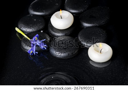 beautiful spa concept top down of iris flower, candles and black zen stones on ripple reflection water - stock photo