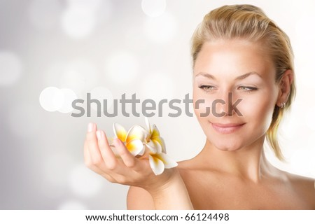 Beautiful Spa Girl with Frangipani flowers - stock photo