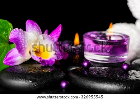 beautiful spa setting of purple orchid dendrobium with dew, black zen stone, green leaf, beads, towels and lilac candles, closeup