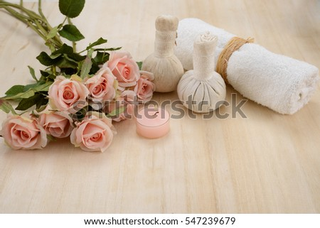 Beautiful spa setting with pink candle and rose, towel ,ball on wooden board