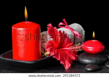 beautiful spa still life of red hibiscus flower with dew, candles and white rolled towel on zen stones - stock photo