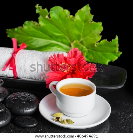 beautiful spa still life of red hibiscus flower with dew, green leaf, cup of tea and rolled towel on zen stones, close up - stock photo