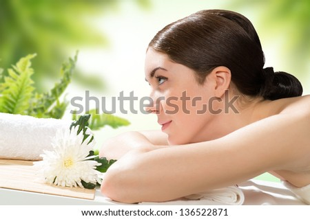 beautiful spa woman lying on the couch, in front of her flower and rolled towel