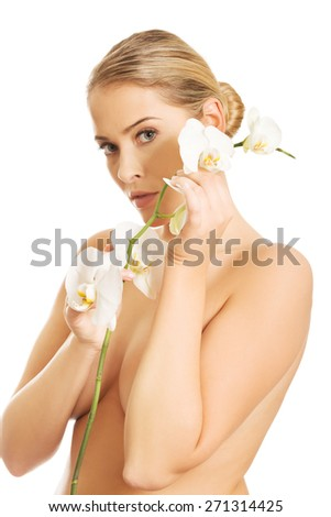 Beautiful spa woman with an orchid flower - stock photo