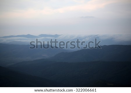 Beautiful spaciousness landscape view from high hill top on many mountain humps with deep green forests and cloudy grey blue sky on natural background, horizontal picture