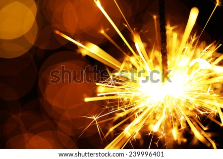 Beautiful sparkler on shiny background, close up - stock photo