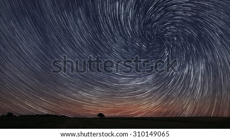Beautiful Spiral Star Trails over filed with lonely tree. Beautiful night sky. - stock photo