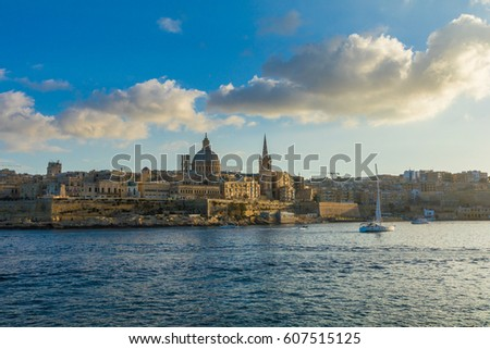 Beautiful spires and cathedral dome of the Valletta skyline under blue sky, golden hour, viewed from Sliema Creek, across Marsamxett Harbour. Valletta, Capital city of Malta