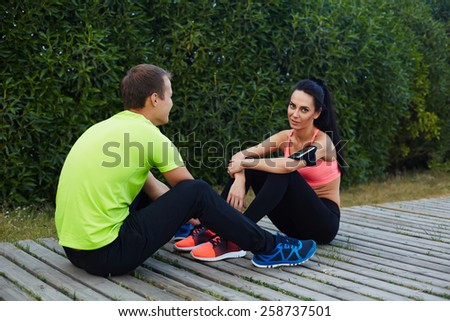 Beautiful sport couple resting after workout sitting in beautiful park, couple in love training together, couple of runners enjoying to each other while they having a rest after workout - stock photo